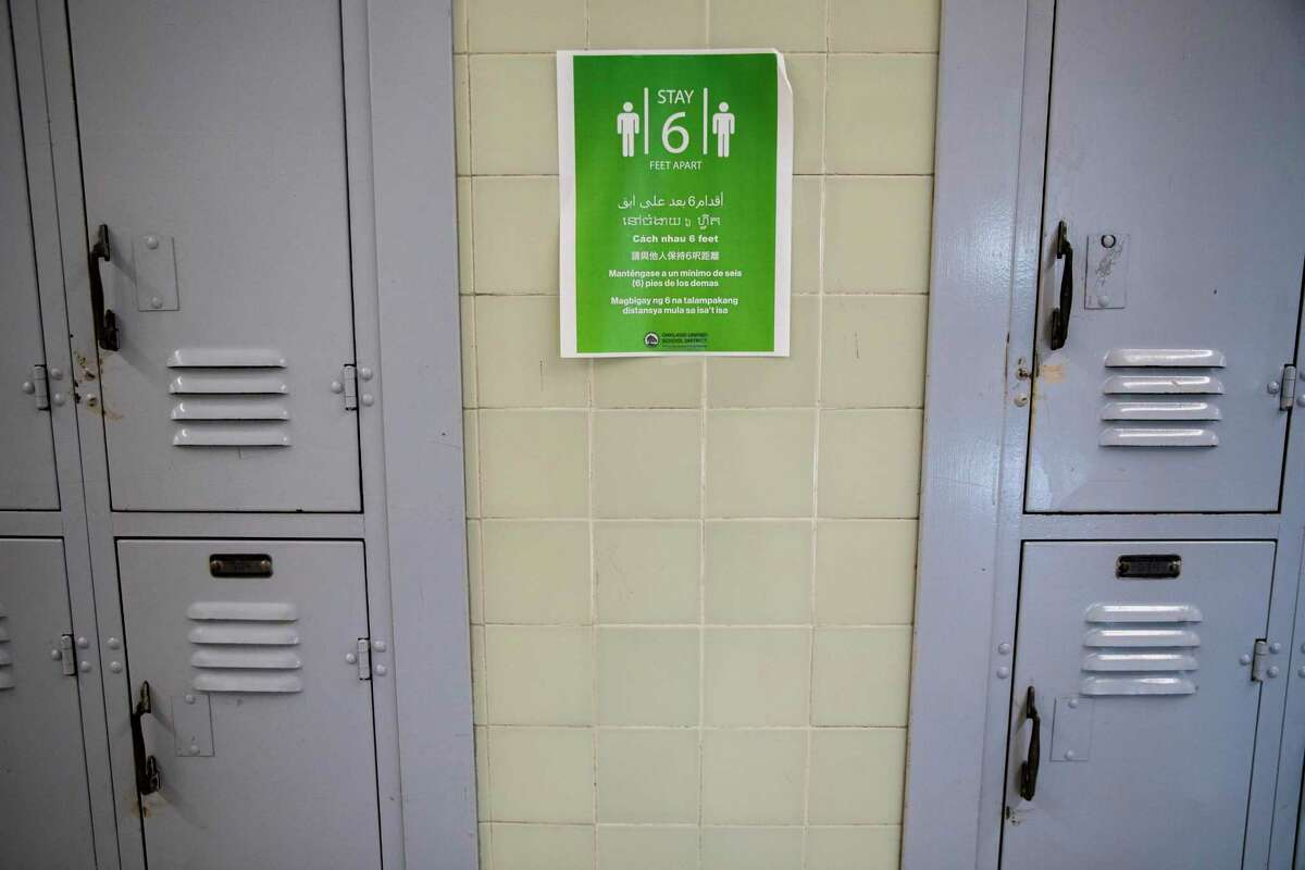 Physical distancing signs are posted inside McClymonds High School in Oakland.