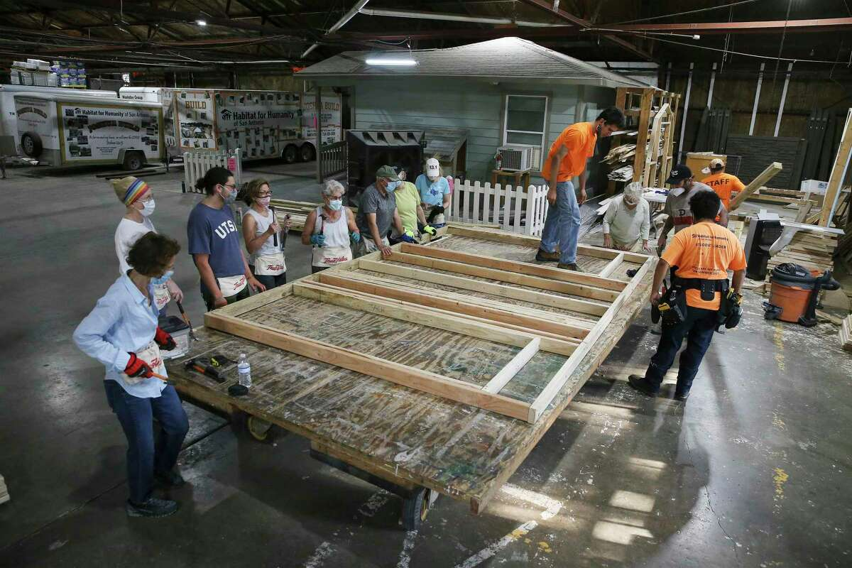 Volunteers from gather to help build a door frame at Habitat for Humanity of San Antonio.