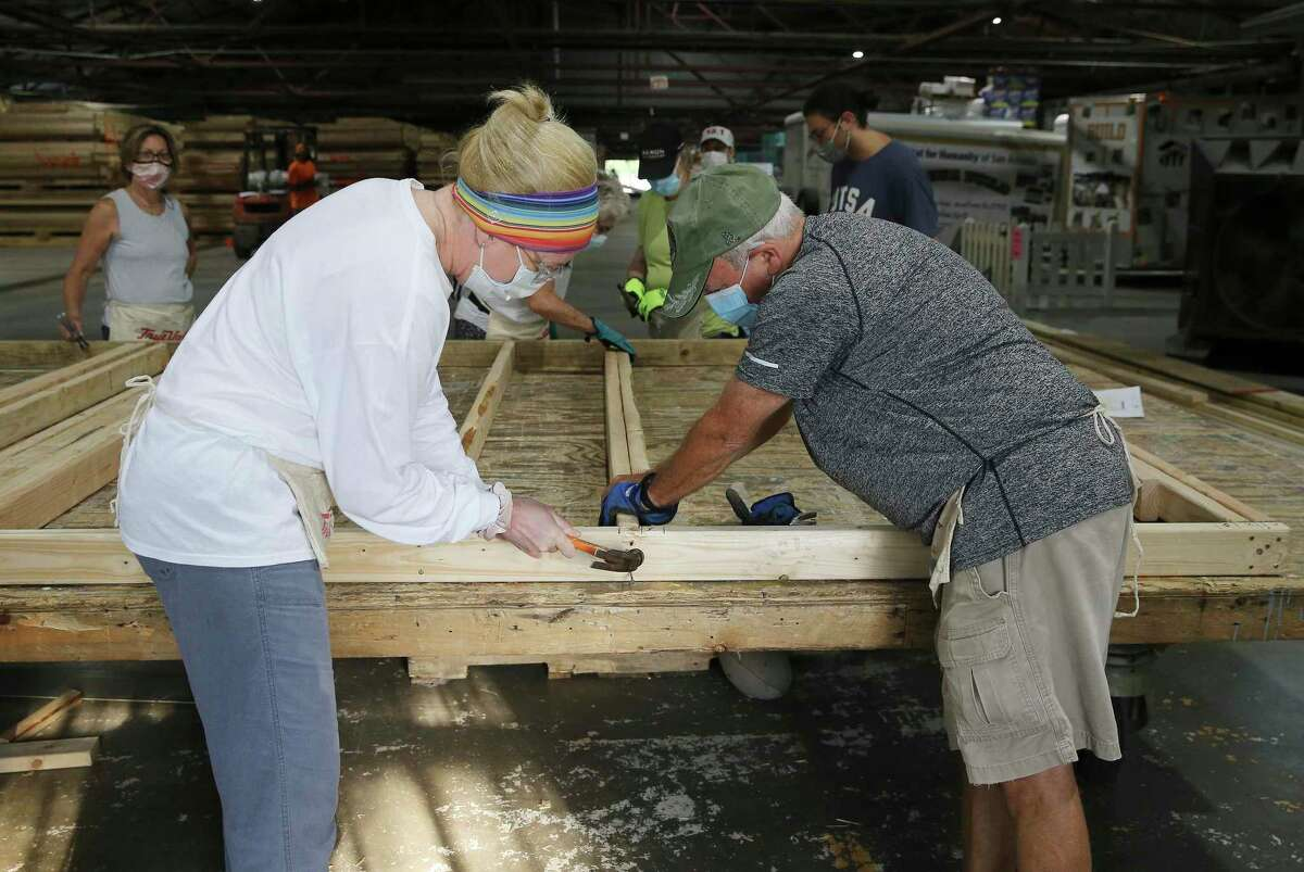 Temple Beth-El volunteers Robert Pollock, right, and Samantha Kennedy join others in nailing together a door frame at Habitat for Humanity of San Antonio.