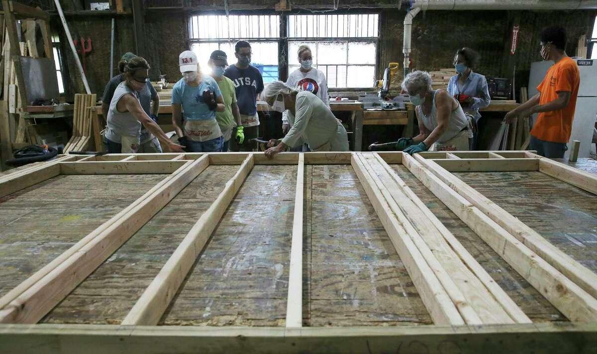 Volunteers from Temple Beth-El help build a door frame at Habitat for Humanity of San Antonio.