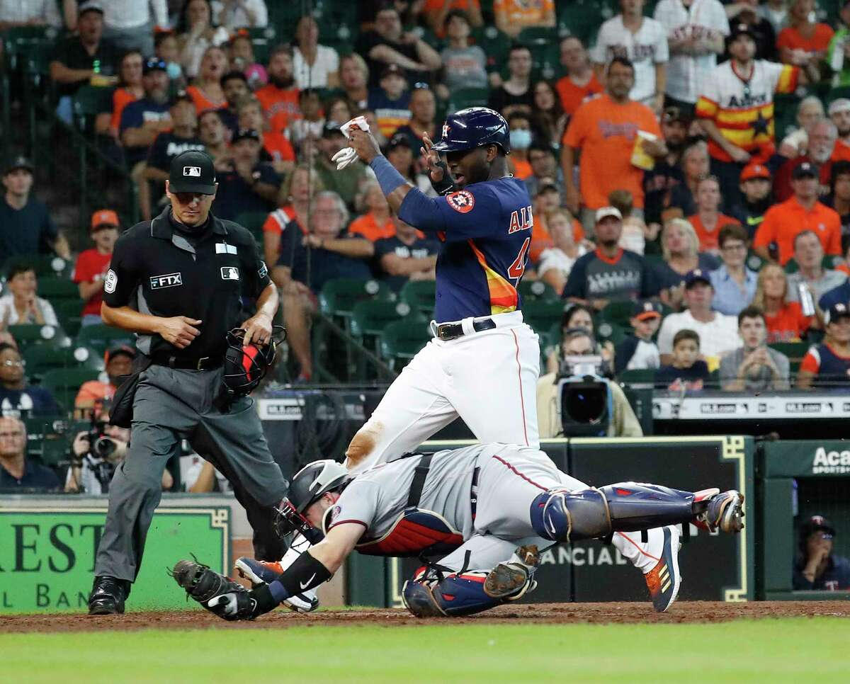 Houston Astros Yordan Alvarez (44) against Minnesota Twins catcher Mitch Garver (8) on Taylor Jones' RBI single during the fourth inning of an MLB baseball game at Minute Maid Park, Sunday, August 8, 2021, in Houston.