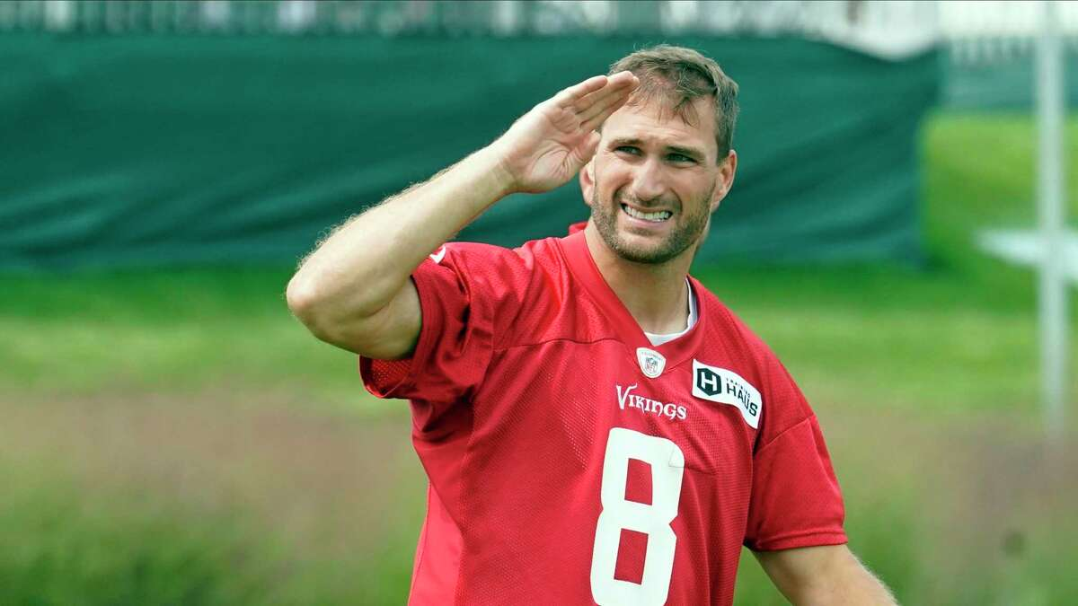 Minnesota Vikings quarterback Kirk Cousins (8) salutes fans as he returned to training camp after a five-day quarantine because of the coronavirus pandemic during the NFL football team's training camp, Thursday, Aug. 5, 2021, in Eagan, Minn. (AP Photo/Jim Mone)
