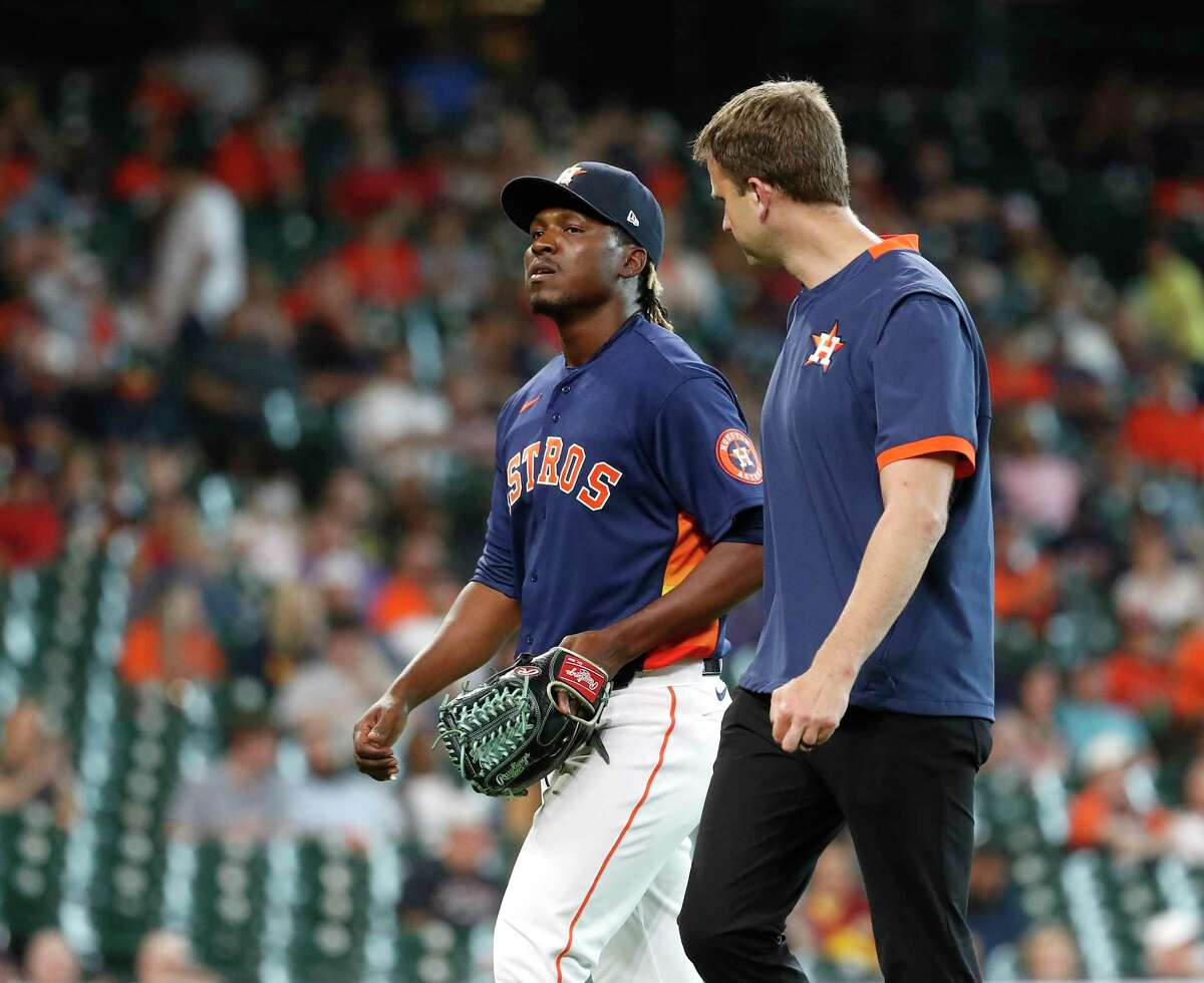 Houston Astros trainer Jeremiah Randall and relief pitcher Rafael Montero (47) walk back to the dugout after Montero suffered an apparent injury during the eighth inning of an MLB baseball game at Minute Maid Park, Sunday, August 8, 2021, in Houston.