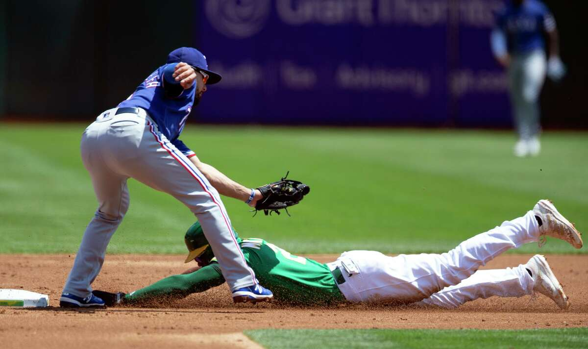 The A's Starling Marte slides into second with a stolen base under the tag of Rangers shortstop Isiah Kiner-Falefa in the first.