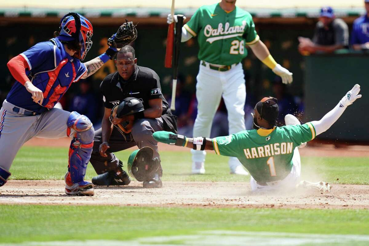 OAKLAND, CALIFORNIA - AUGUST 08: Josh Harrison #1 of the Oakland Athletics slides safely past Jonah Heim #28 of the Texas Rangers into home plate during the first inning at RingCentral Coliseum on August 08, 2021 in Oakland, California. (Photo by Ben Green/Getty Images)