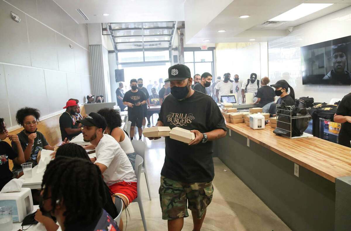 Bun B runs burgers to people Sunday, Aug. 8, 2021, at Sticky's Chicken in Houston. Bun B partnered with Andy Nguyen, Patsy Vivares and her brother Benson to open a new burger concept called Trill Burgers, which held an event at Sticky's Chicken.