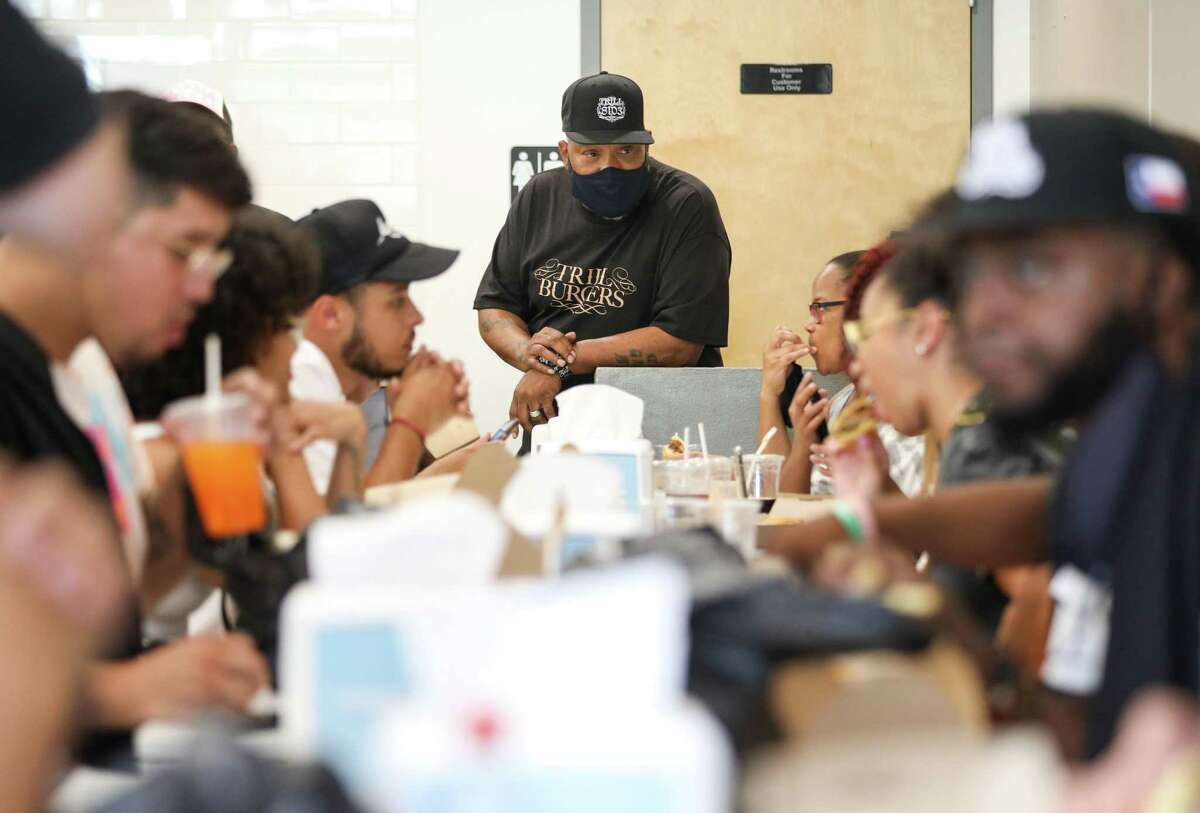 Bun B talks with patrons as they eat Sunday, Aug. 8, 2021, at Sticky's Chicken in Houston. Bun B partnered with Andy Nguyen, Patsy Vivares and her brother Benson to open a new burger concept called Trill Burgers, which held an event at Sticky's Chicken.