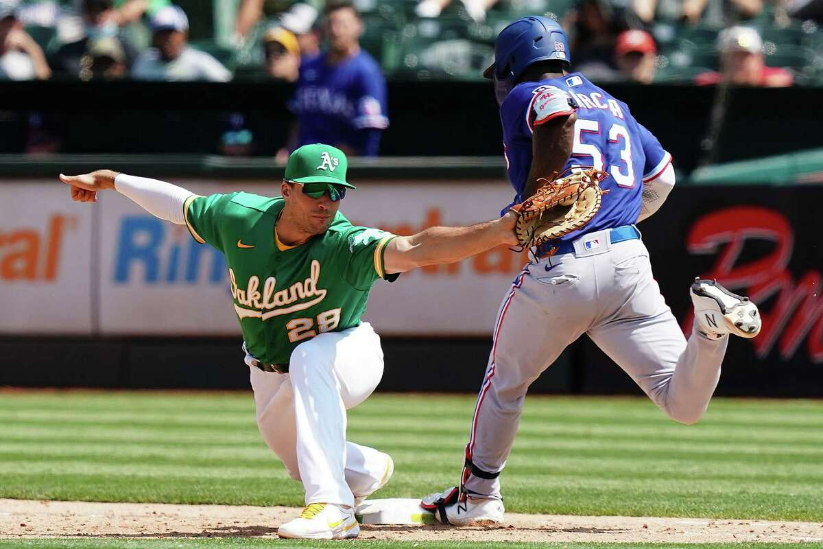 OAKLAND, CALIFORNIA - AUGUST 08: Matt Olson #28 of the Oakland Athletics forces Adolis Garcia #53 of the Texas Rangers out at first during the sixth inning at RingCentral Coliseum on August 08, 2021 in Oakland, California. (Photo by Ben Green/Getty Images)