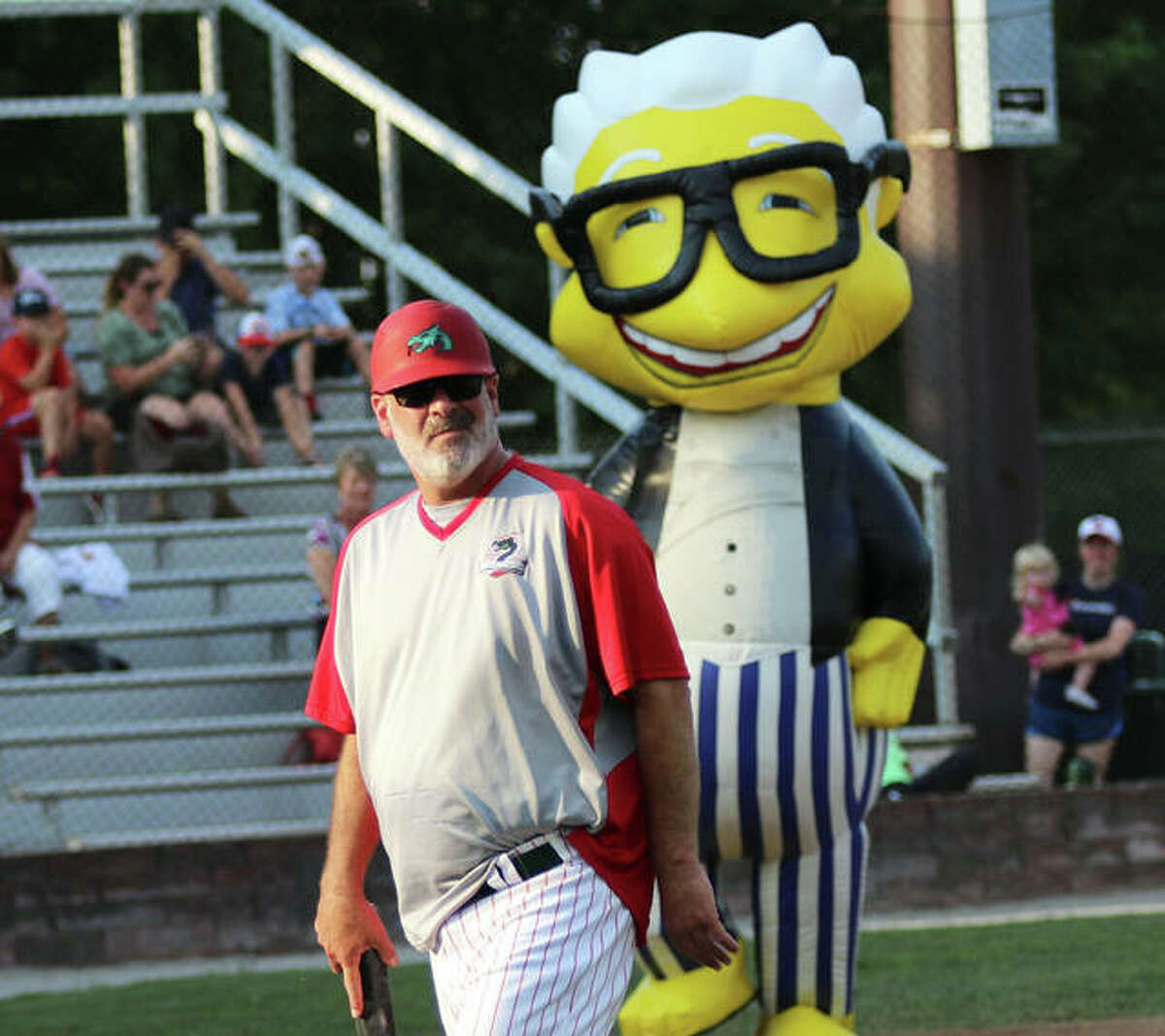 Alton River Dragons manager Darrell Handelsman walks back to the dugout between innings on ZOOsuperstars Night with mascot Harry Canary entertaining the crowd during a July 9 game at Hopkins Field in Alton.