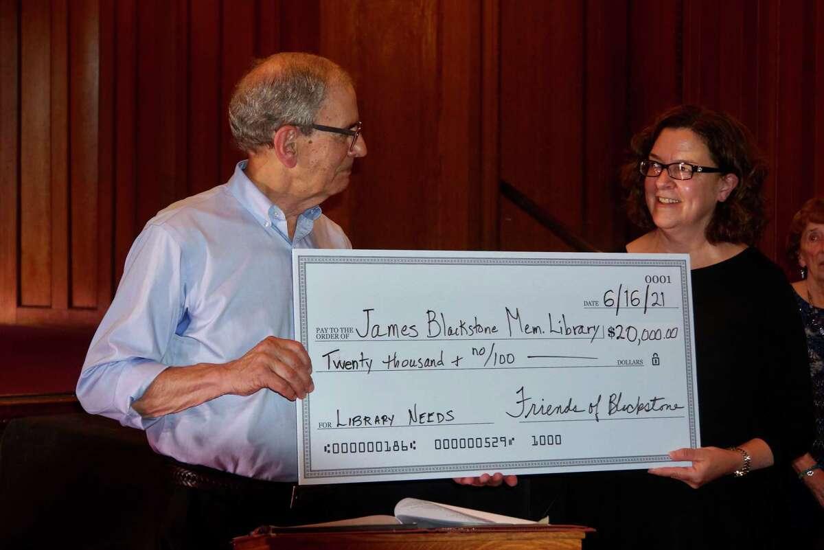 Alfred Bertoline, representing the Friends of Blackstone Library, presents a $20,000 check to Karen Jensen, library director.