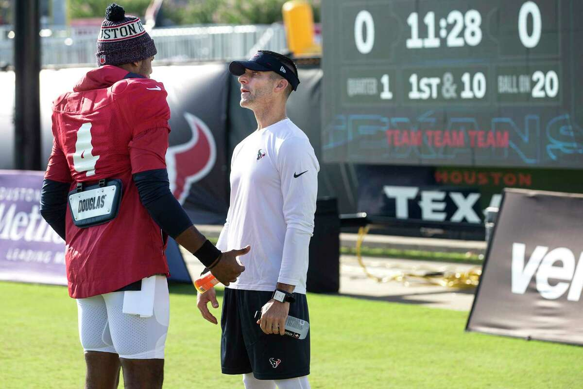 Houston Texans quarterback Deshaun Watson (4) talks to general manager Nick Caserio during an NFL training camp football practice Monday, Aug. 9, 2021, in Houston.