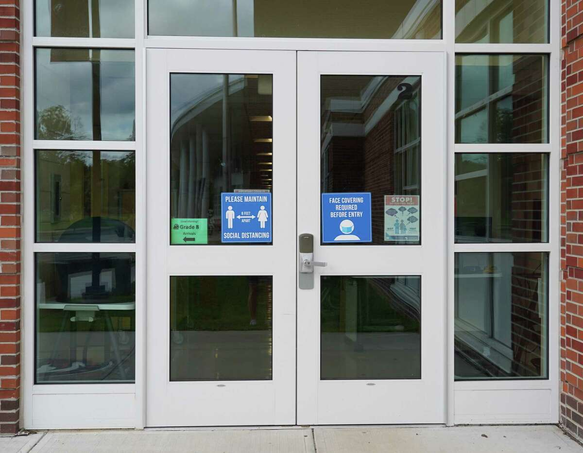 A sign on the door at Saxe Middle School in New Canaan says masks are required on Aug. 5, 2021
