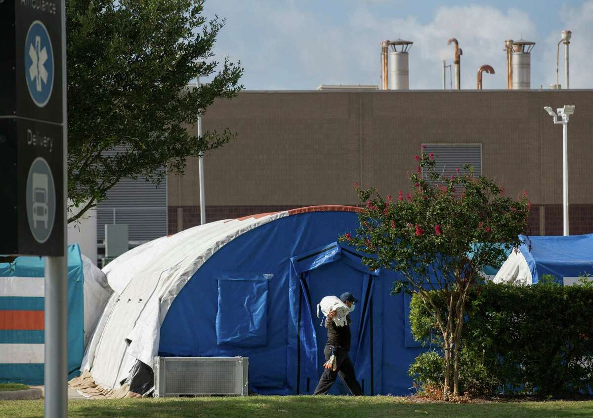 A construction crew works to setup tents to deal with overflow COVID-19 patients outside Lyndon B. Johnson Hospital on Monday, Aug. 9, 2021, in Houston.
