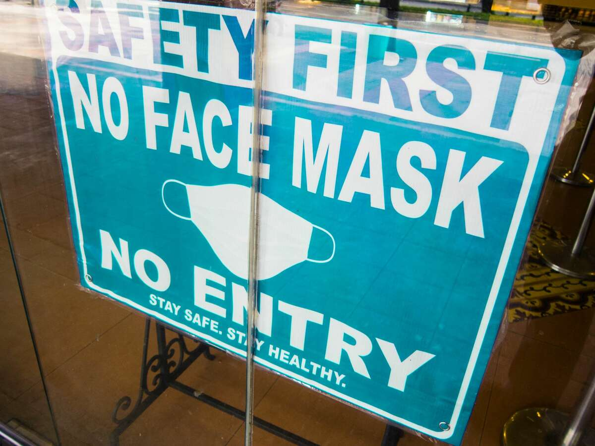 Close-up view of No Mask No Entry sign in a store window amidst COVID-19 pandemic.