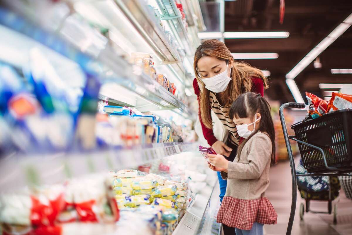 Pictured is a mom & her daughter, both with surgical masks doing grocery shopping for diary products in front of a refrigerator in supermarket.