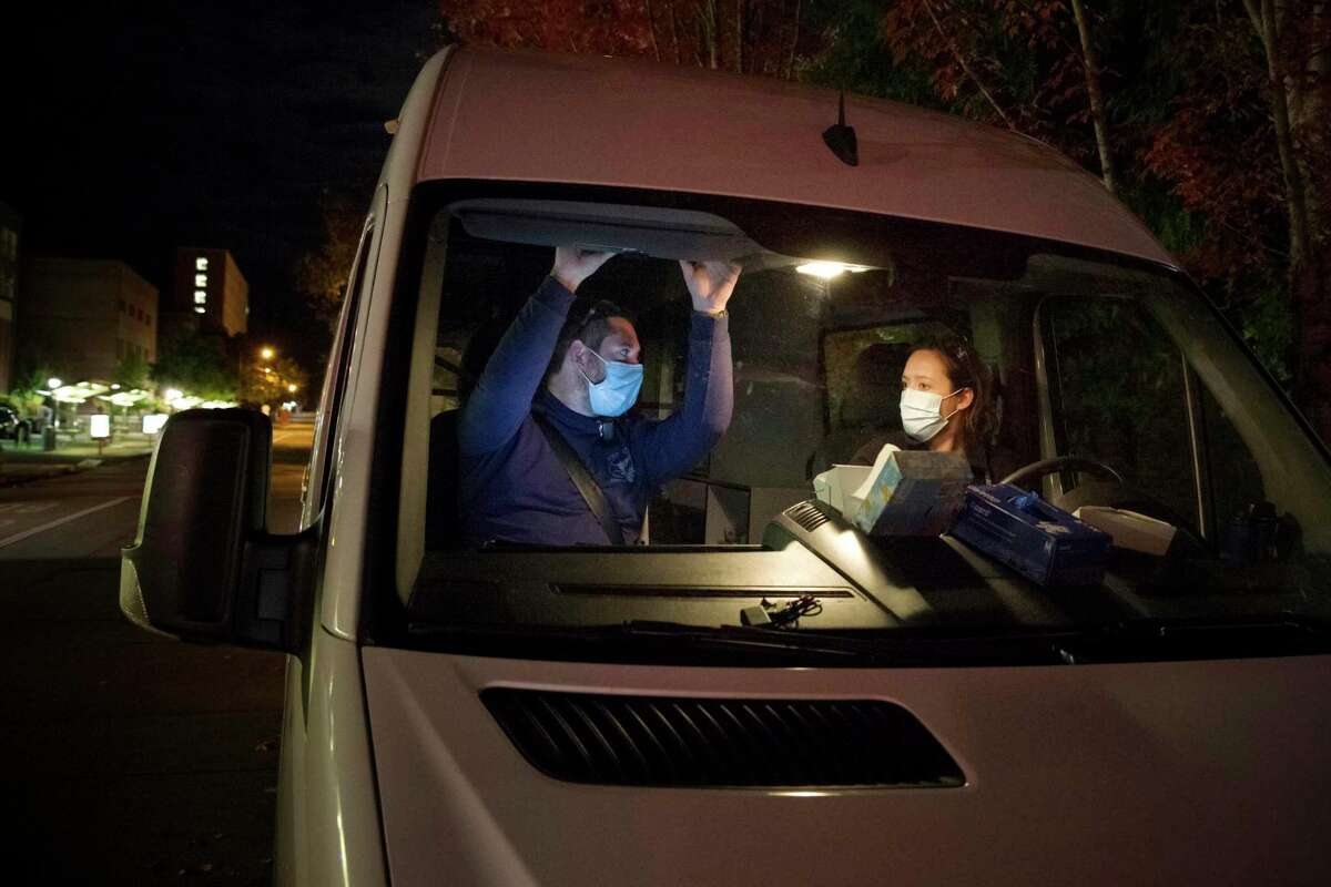 Emergency Medical Technicians Henry Cakebread and Ashley Barnhill-Hubbard with CAHOOTS, a mental health crisis intervention program, discuss their last encounter during their night shift in Eugene, Ore. in October 2020. A government health program helped communities set up mobile teams of practitioners trained in de-escalating potentially volatile situations. Harris County is planning a similar program.