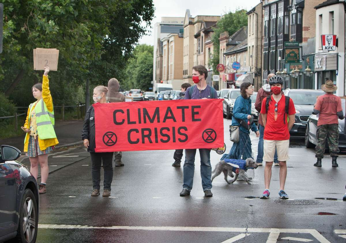 Extinction Rebellion activists in Cambridge, UK blocked a major road in five minute intervals in order to stop the traffic and highlight the extreme weather events from this year and the way the climate is changing. (Photo by Martin Pope/SOPA Images/LightRocket via Getty Images)