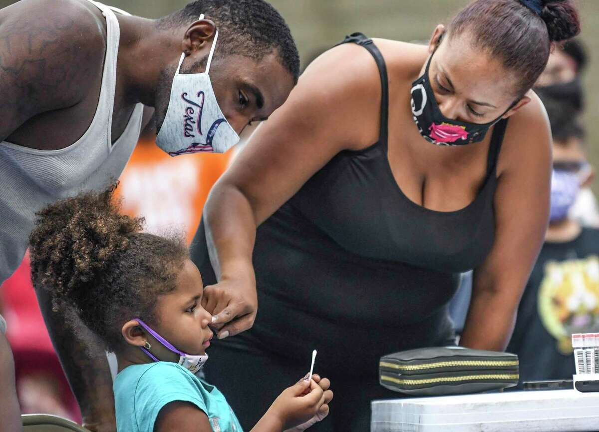 A mother tests her daughter for COVID earlier this month. Many readers are outraged that Gov. Greg Abbott is fighting schools and local governments from mandating masks, especially for children too young to be vaccinated.