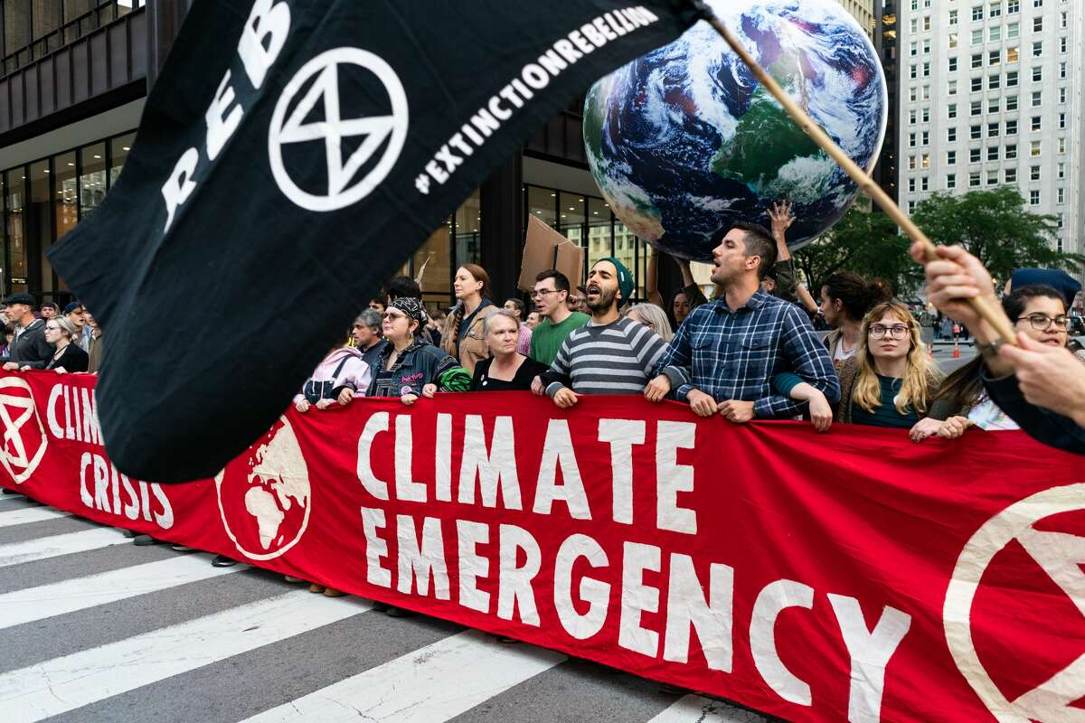 Demonstrators shut down the corner of Randolph and Clark streets as part of a protest demanding government action on climate change in Chicago on October 7, 2019. (Photo by Max Herman/NurPhoto via Getty Images)
