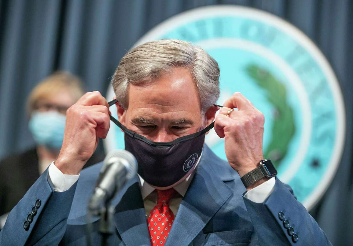 Texas Gov. Greg Abbott takes off his mask during a press conference on Thursday, Sept. 17, 2020.