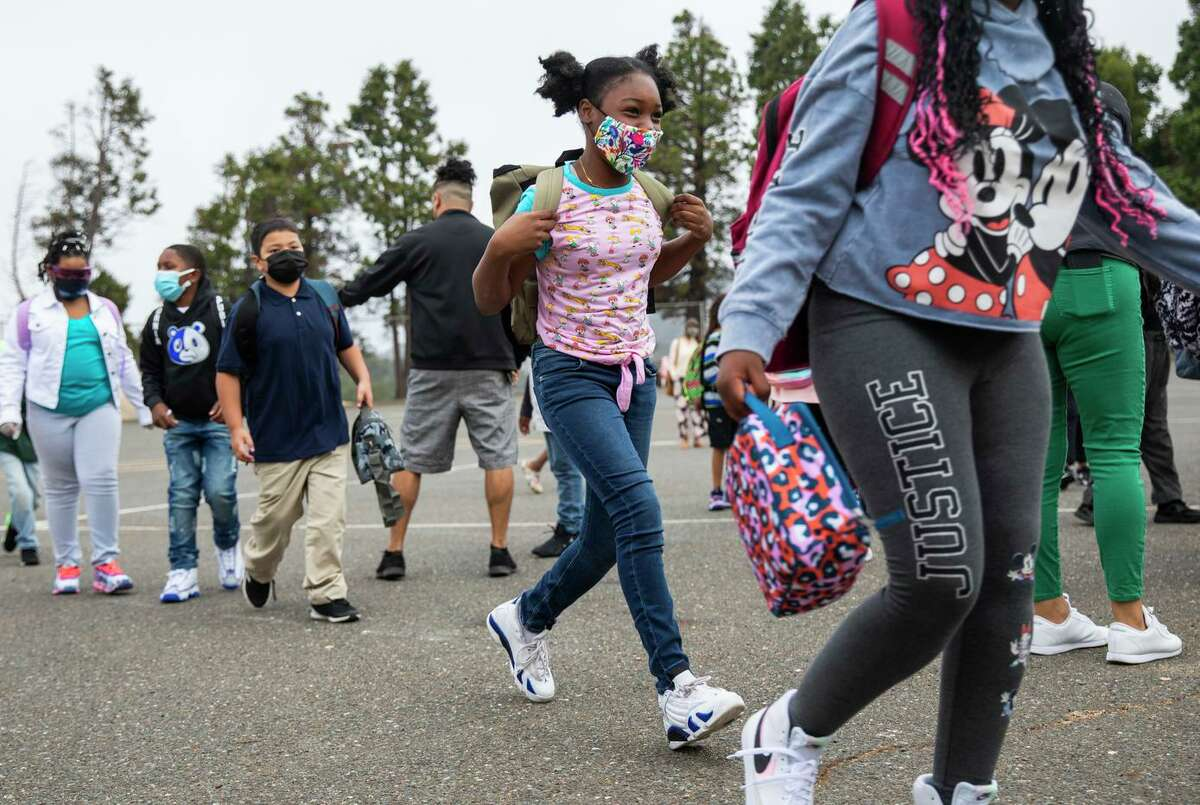Fifth-grade students run before the start of the first day at Howard Elementary School. Masks are required indoors on Oakland school district campuses and recommended outdoors.
