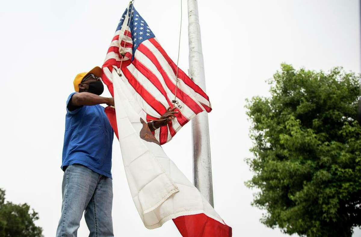 Oakland resident and veteran Ken McNeal raises flags as students arrive for the first day at Howard Elementary School.