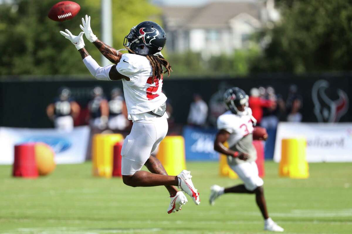 Houston Texans cornerback Bradley Roby (21) leaps to catch a ball during an NFL training camp football practice Monday, Aug. 9, 2021, in Houston.
