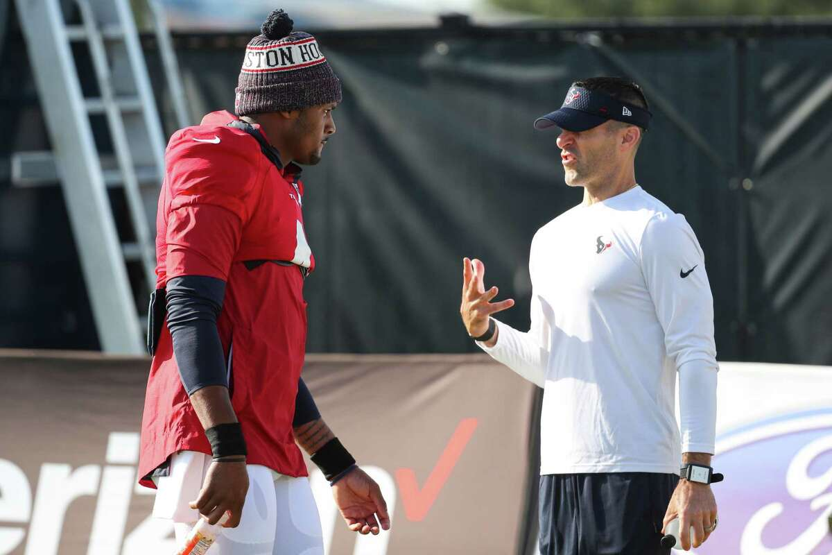 Houston Texans quarterback Deshaun Watson (4) stops to talk to general manager Nick Caserio during an NFL training camp football practice Monday, Aug. 9, 2021, in Houston.