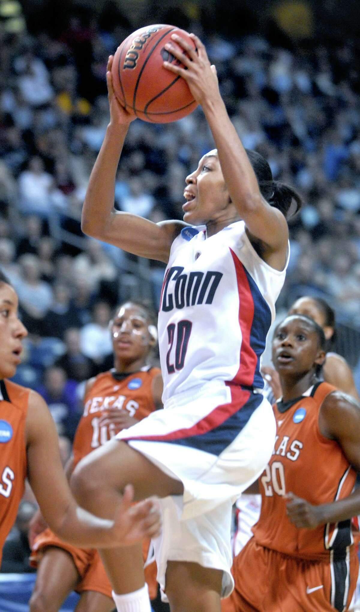 Renee Montgomery (center) of UCONN drives to the basket against Texas in the first half of the second round of the NCAA tournament in Bridgeport on 3/25/2008.
