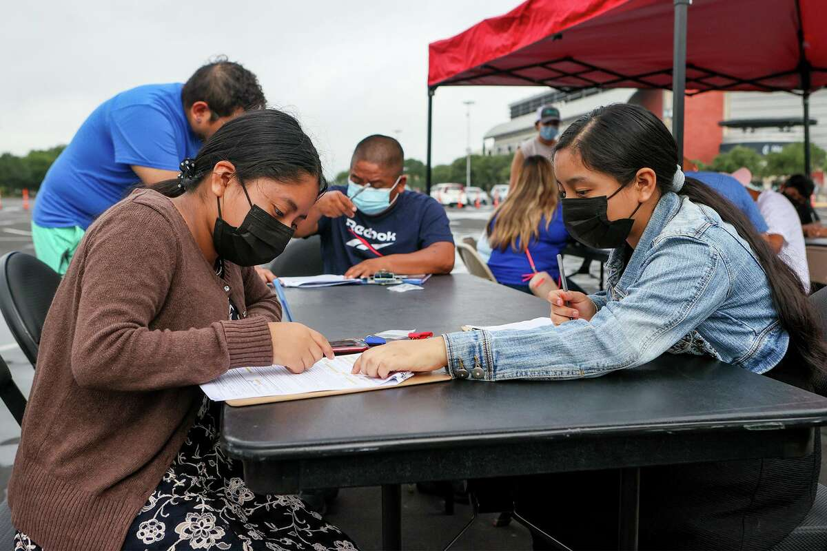 Jessica Mendez, 13, right, helps her sister, Jennifer Mendez, 14, complete a registration form in July at the AT&T Center, where the city and the Spurs hosted an event to encourage residents to get vaccinated against COVID-19.