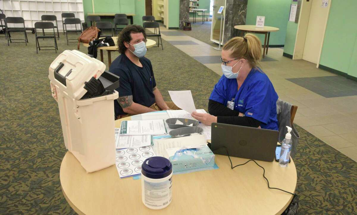 EMT Eugenia McGovern, from Griffin Health, gathers information from Anthony Capirichio, of Danbury, who was a walk-in to the COVID-19 vaccine clinic held in the Danbury Public Library on Friday, April 30, 2021, in Danbury, Conn. The city and other experts are encouraging COVID vaccines.