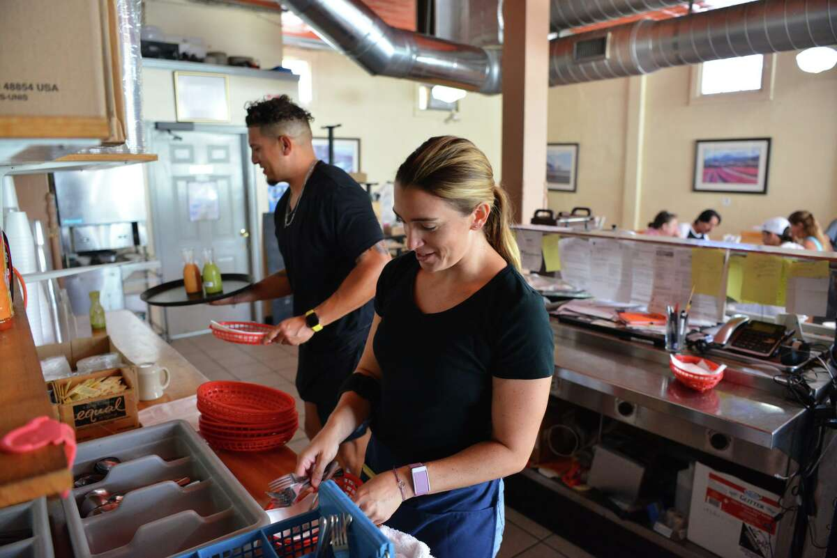 Volunteers and customers Alyson Fitzpatrick and Ernest Ramos prepare orders at Panchos & Gringos restaurant.