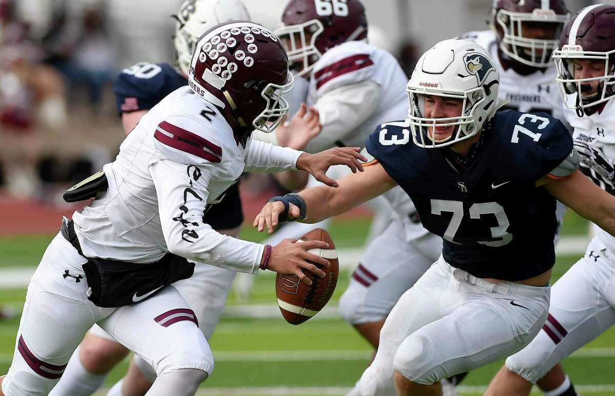 Saint Michael's quarterback Daniel Serna, left, tries to run past Second Baptist defensive lineman Colin Hedges (73) during the second half of a TAPPS Division II regional high school football playoff game, Saturday, Dec. 5, 2020, in Columbus, TX.