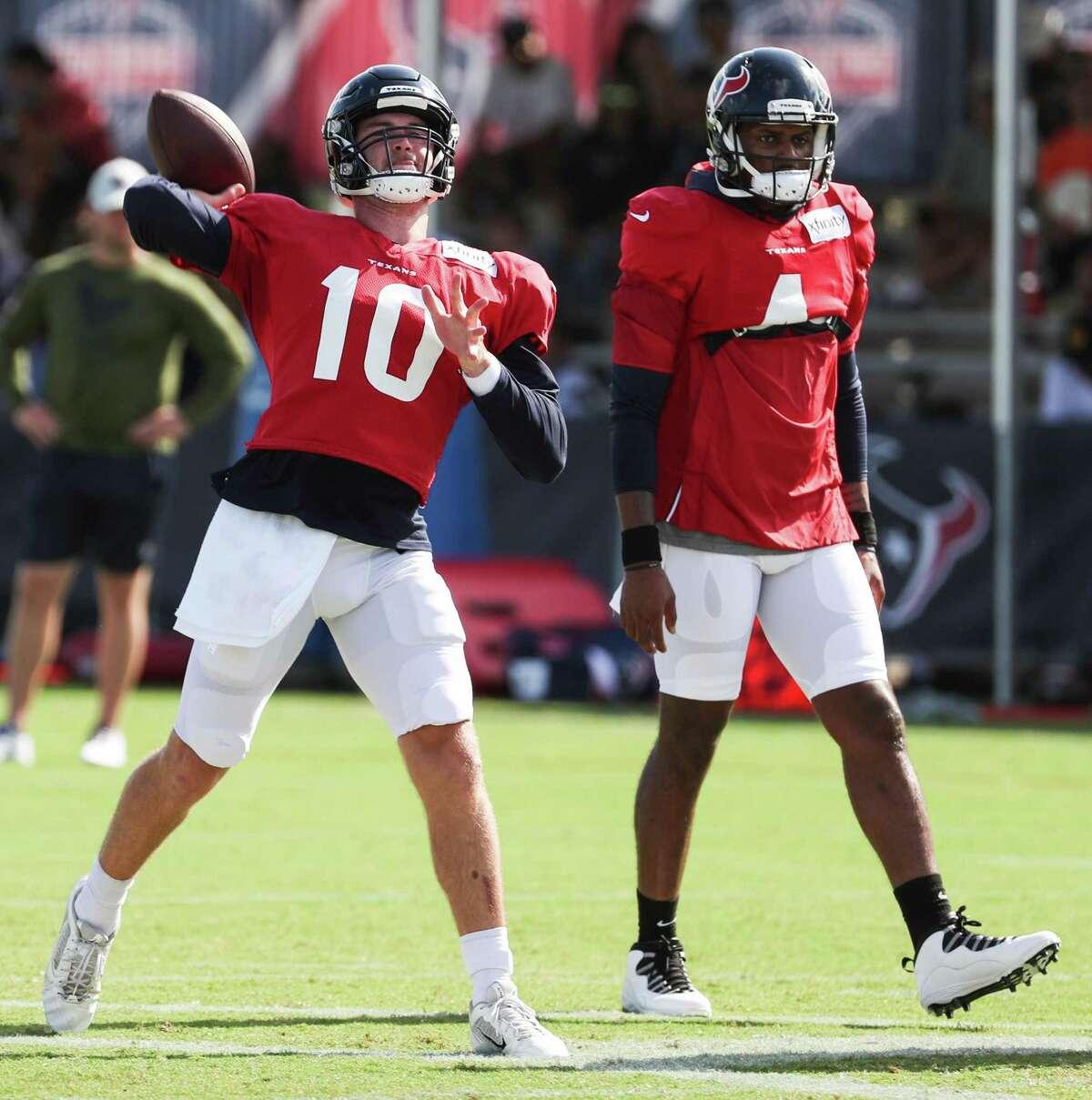 Houston Texans quarterback Davis Mills (10) throws a pass while working with quarterback Deshaun Watson (4) during an NFL training camp football practice Monday, Aug. 9, 2021, in Houston.