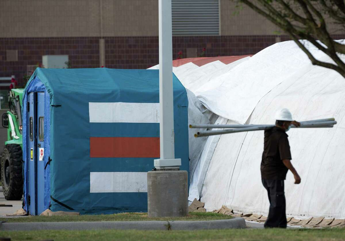 A construction crew works to setup tents in case of overflow COVID-19 and ICU patients outside Lyndon B. Johnson Hospital on Monday, Aug. 9, 2021, in Houston.