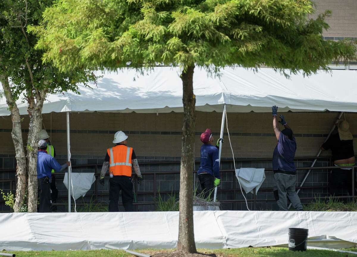 A construction crew works to setup tents to make room for a possible overflow of patients outside Lyndon B. Johnson Hospital on Monday, Aug. 9, 2021, in Houston.