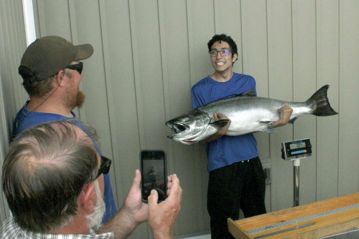 In a photo from Saturday, Aug. 7, 2021, Louis Martinez, 19, of Ortonville, holding a new Michigan state record Chinook salmon; a 47.86-pound, 47 1/2-inch Chinook. (David Bossick/Ludington Daily News via AP)