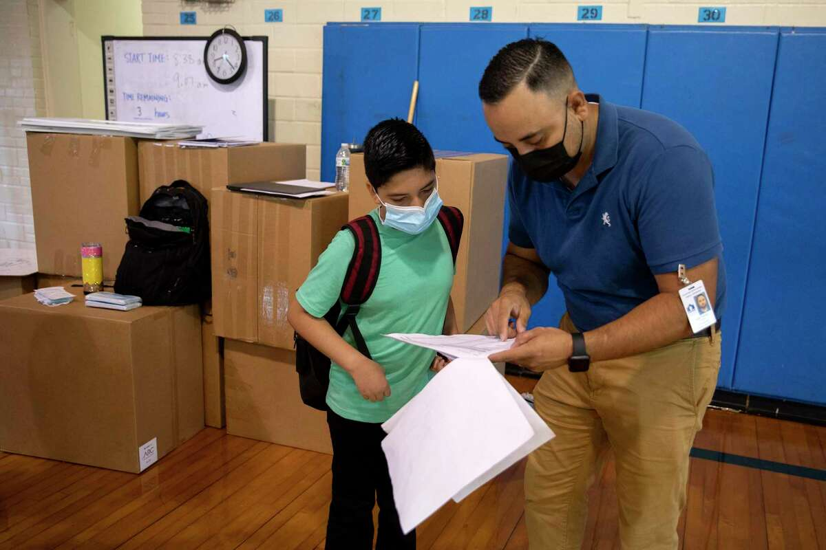 A Hot Wells Middle School social studies teacher, Jorge Frausto, helps 7th grader Eddy Garrido figure out where to go on the first day of school.