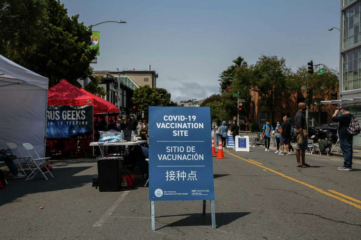 A sign directs people to a COVID-19 vaccination site and and testing tent during the annual Nihonmachi Street Fair in San Francisco.