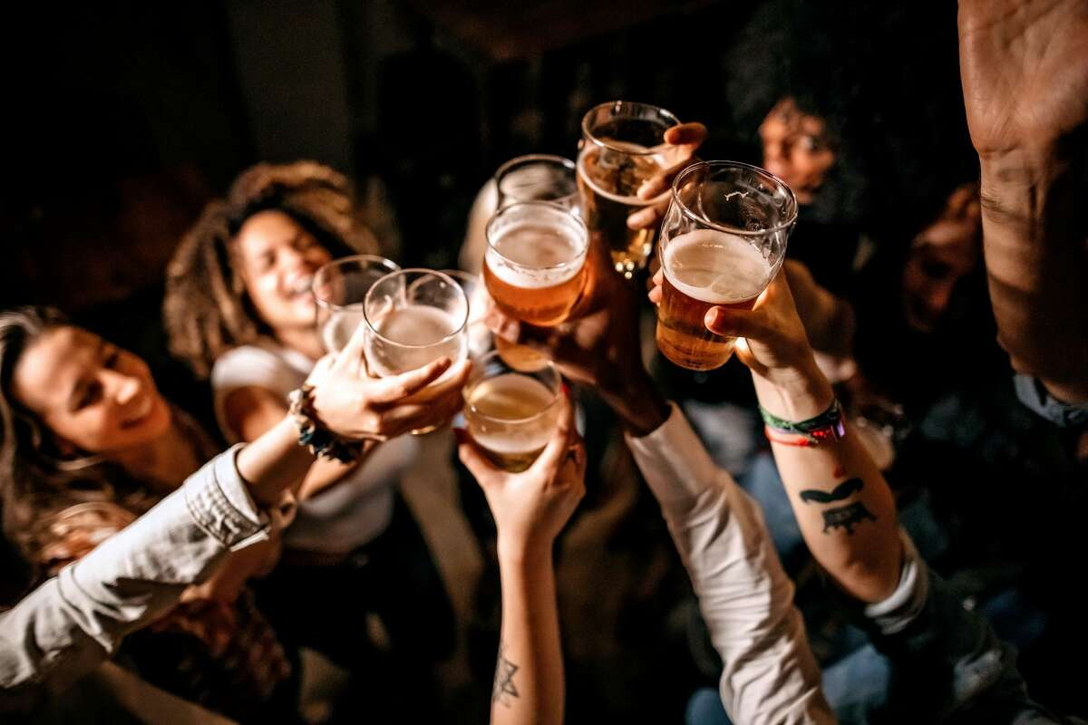 Excited friends are pictured toasting with beer glasses at a pub.