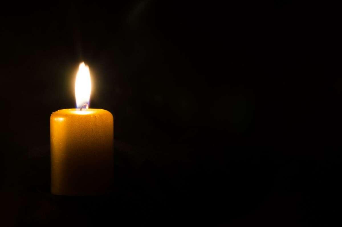 one burning candle decoration against black background FOTOLIA