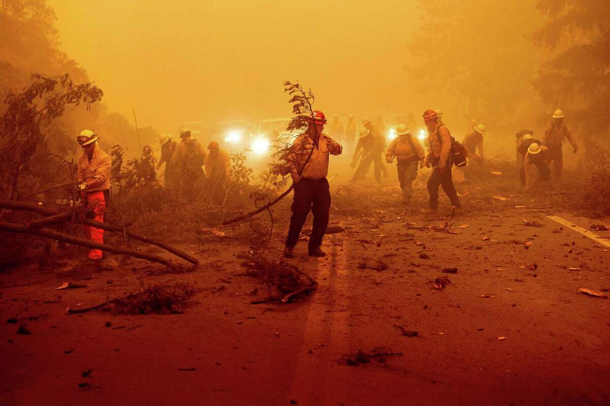 Firefighters battling the Dixie Fire clear Highway 89 after a burned tree fell across the roadway in Plumas County, Calif., on Friday, Aug. 6, 2021. (AP Photo/Noah Berger)