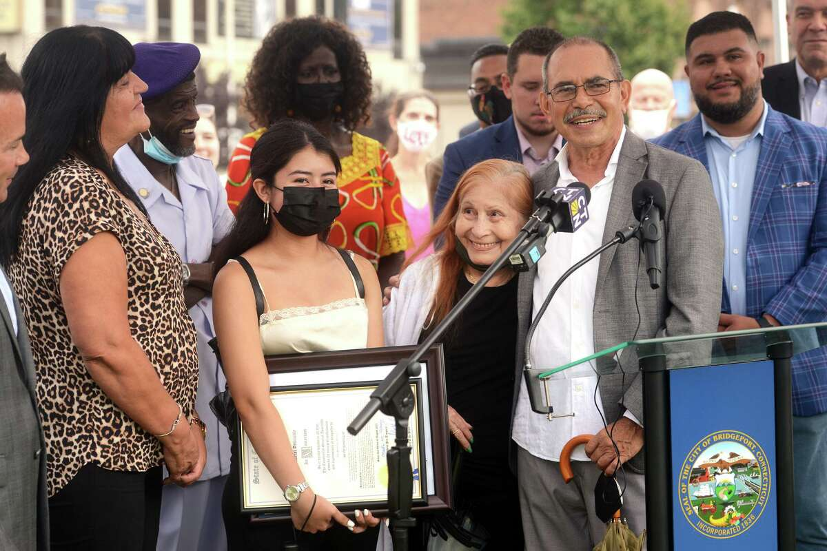 Former State Rep. Ezequiel Santiago's father, Americo Santiago, right, stands hugs his mother, Lydia Mercado, while he speaks during a ceremony in Bridgeport, Conn. Aug. 9, 2021. It was announced that a portion of Fairfield Avenue, in Bridgeport, will now hold the honorary name of State Representative Ezequiel Santiago Memorial Highway, in memory of the legislator who died in 2019. They are seen here with Ezequiel's mother, Evelyn Robles, left, and his daughter, Chelsie Morales-Santiago.