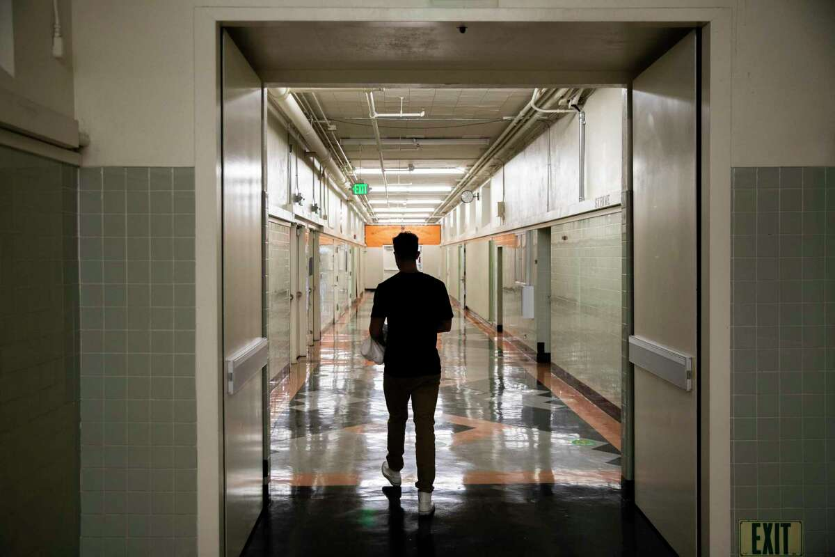 Braden DeWitt walks to his classroom to prepare it for physical distancing at McClymonds High School in Oakland, Calif.