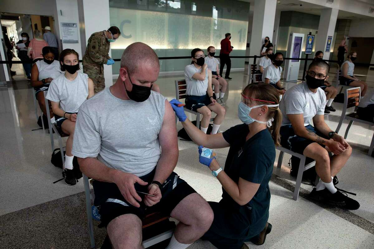 Air Force recruits in their first week of basic training receive the first dose of the Pfizer vaccine at Lackland Air Force Base. The vaccine is optional for all recruits, but will be mandatory for the entire military under a directive issued Monday by the secretary of defense.
