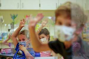 This Tuesday May 18, 2021 file photo shows kindergarten students wearing face masks and separated by plexiglass during a math lesson at the Milton Elementary School in Rye, N.Y. (AP Photo/Mary Altaffer)