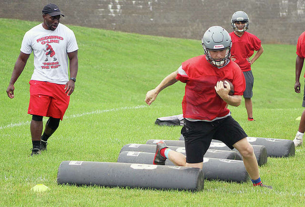 Alton's Gage DePew runs through a footwork drill under the guidance of AHS assistant coach Jessie Riley, left, Monday morning at Alton High School. Monday was the first IHSA-sanctioned day of preseason practice for fall sports, including football.