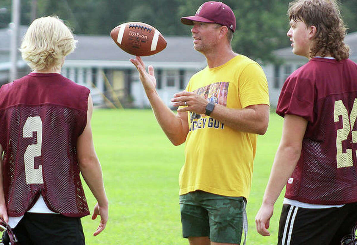 East Alton-Wood River assistant coach Derek Forsting twirls a football on his fingertip as he talks with senior quarterback Chase Keshner (2) and Brayden st. Peters (24) Monday at the Oilers' first practice of the season.
