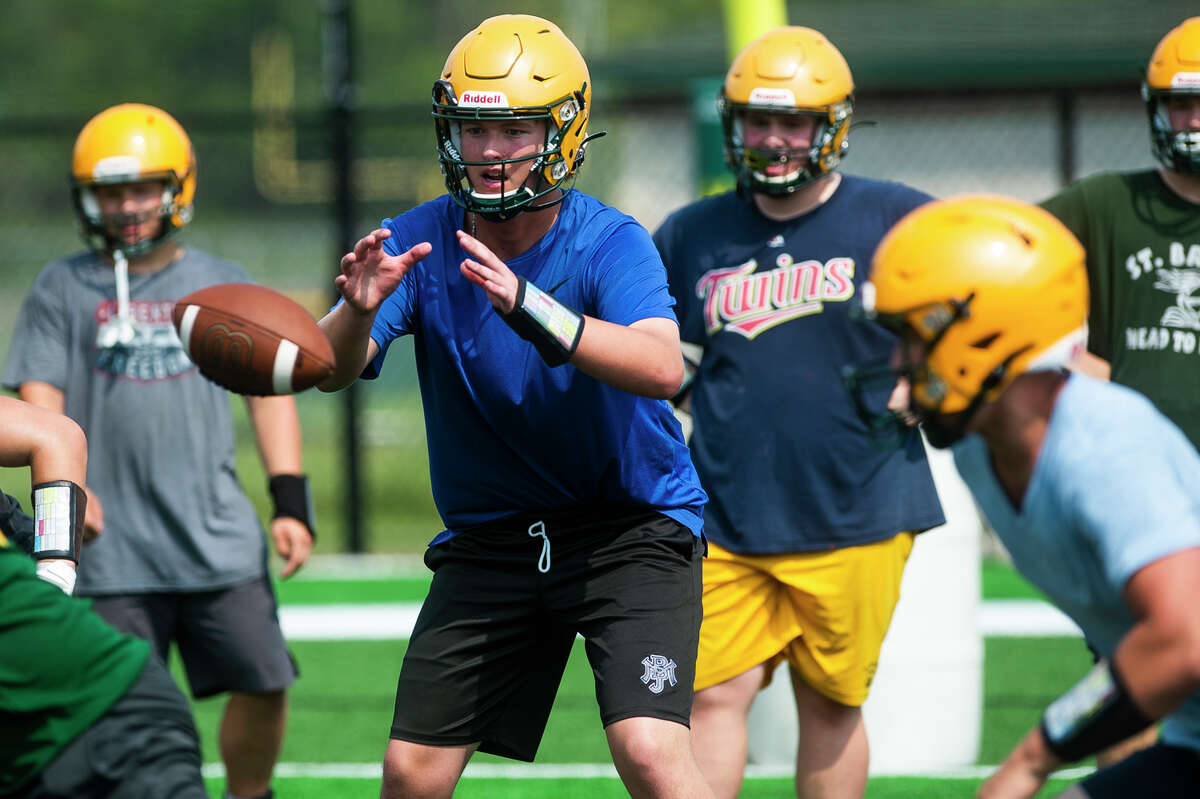 The ball is hiked to Dow's Jack Bakus during the Chargers' first football practice of the year Monday, Aug. 9, 2021 at H. H. Dow High School. (Katy Kildee/kkildee@mdn.net)
