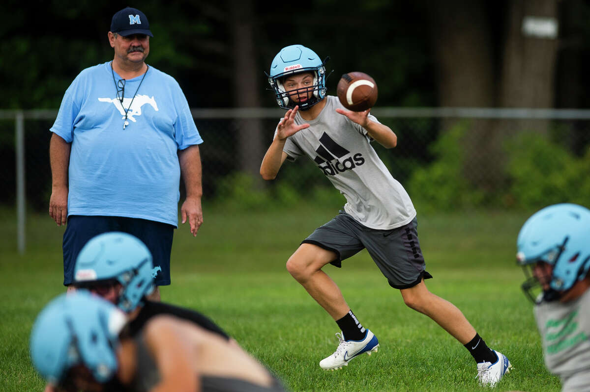 Meridian's Eli Olmstead catches a pass during the Mustangs' first varsity football practice of the year Monday, Aug. 9, 2021 at Meridian Early College High School in Sanford. (Katy Kildee/kkildee@mdn.net)